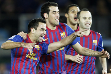 Xavi of Spain's Barcelona celebrates a goal against Brazil's Santos with his teammates Busquets, and Iniesta during their Club World Cup final soccer match in Yokohama