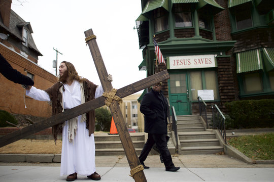 """As a pedestrian looks on, Michael Grant, 28, """"Philly Jesus,"""" hands a supporter his iPhone and headphones after saying goodbye to a friend, while holding a 12 foot cross which he carried 8 miles through North Philadelphia"""