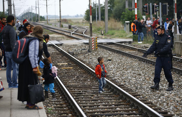 A policeman keeps a migrant's child away from the tracks at the train station in Nickelsdorf