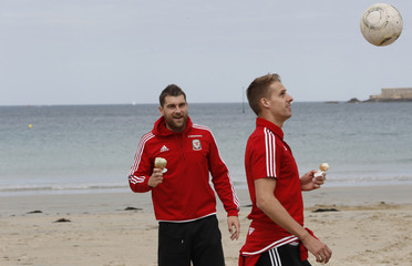Wales' Edwards and Voke eat an icecream as they walk on the beach in Dinard