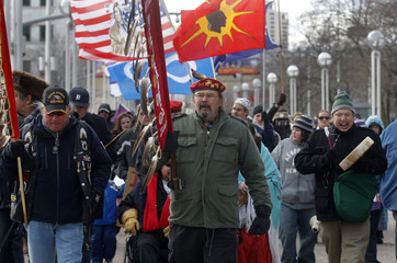 Native Americans Mike Burja and Wayne Hardwick carry eagle staffs as they lead a group of Native Americans and supporters in a demonstration in support of the 'Idle No More' First Nations Canadian movement in downtown Detroit