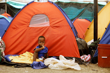 An African migrant children stranded in Costa Rica, sits outside his tent at makeshift camp at the border between Costa Rica and Nicaragua, in Penas Blancas