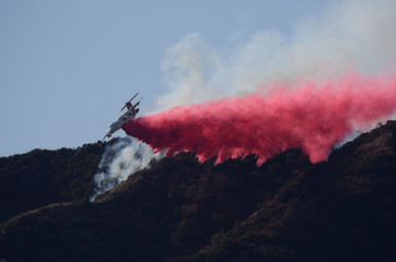 A fire fighting aircraft drops fire retardant over one of two wildfires in the Angeles National Forest above Azusa, California