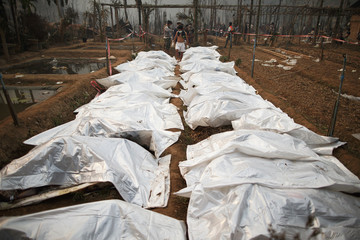 A man walks between body bags of victims of the fire at the Ban Mae Surin refugee camp near Mae Hong Son