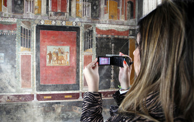 A woman takes a picture at the domus of Marc Lucretius Frontone at the ancient archaeological site of Pompeii