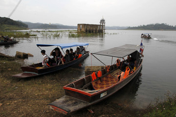 Tourists take a long-tail boat to the site of the Wiwekaram temple near the Thailand-Myanmar border in the Sangkla Buri district