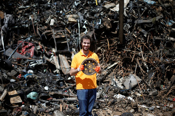 Jordanian graphic designer Abdelrahman Asfour, who turns car parts into furniture, smiles after he found a car part while looking through car parts at a junk yard in Amman, Jordan