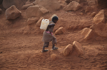A girl from the Burji ethnic tribe carries a jerry can of water back to  her home near Marsabit