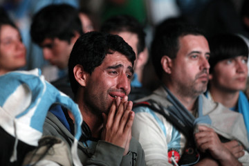 Argentina's fans react after Argentina lost to Germany in their 2014 World Cup final soccer match in Brazil, at a public square viewing area in Buenos Aires