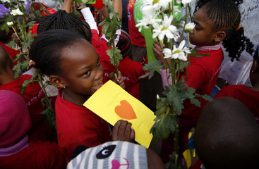Children hold cards and flowers as they gather to wish to former President Nelson Mandela happy birthday