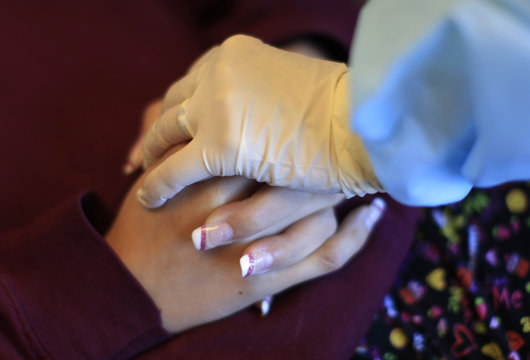 Janet Zamora has her hands held by dental assistant Ramora Ory at Comprehensive Dentistry in Bloomingdale