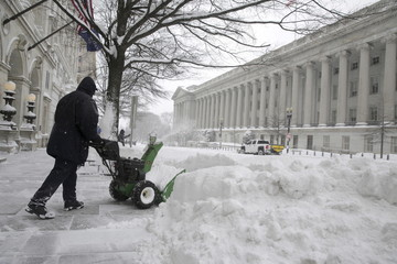 A man uses a snow blower to clear snow during a winter storm in Washington