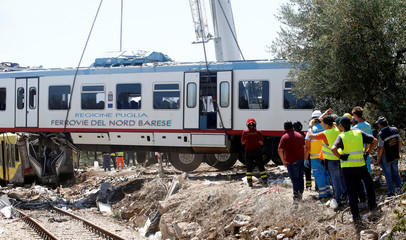 Rescuers work at the site where two passenger trains collided in the middle of an olive grove in the southern village of Corato