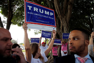 Supporters of U.S. Republican presidential nominee Donald Trump gather as U.S. Democratic presidential nominee Hillary Clinton greets voters and activists outside an early voting location in Pompano Beach