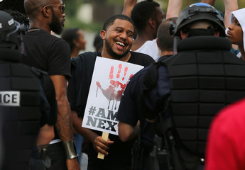 A demonstrator shares a laugh with a police officer in riot gear as people protest the police shooting of Keith Scott, outside the football stadium where the NFL's Carolina Panthers are hosting the Minnesota Vikings in Charlotte