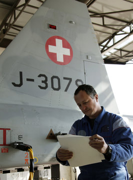 Worker Jean-Marc Cheneaux folds a filter of a Swiss Air Force F-5E Tiger aircraft in Payerne after a radioactivity measurements flight over Switzerland