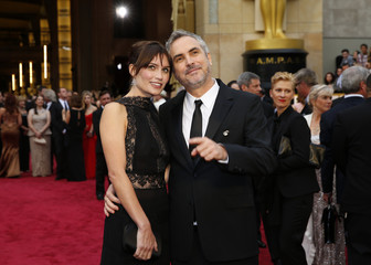 Mexican Director, Aflonso Cuaron, and his partner Sheherazade Goldsmith arrive on the red carpet at the 86th Academy Awards in Hollywood