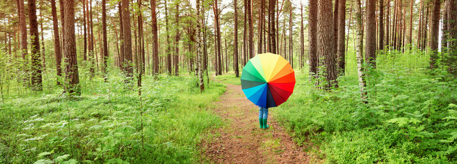 Childg in the park with colourful umbrella. Boy in rainy weather in the forest