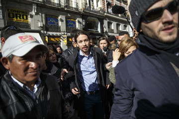 Pablo Iglesias, Secretary General of Spanish Podemos party, walks away surrounded by people after the shooting of a video at Puerta del Sol square in Madrid