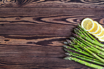 Bunch of fresh green asparagus spears and lemon on a rustic wooden table