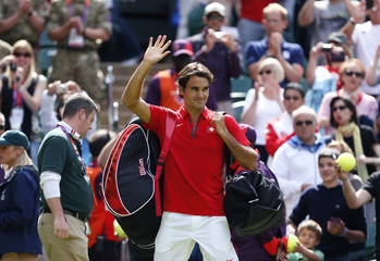 Switzerland's Federer waves to spectators after defeating France's Benneteau in their men's singles tennis match at the All England Lawn Tennis Club during the London 2012 Olympics Games