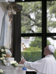 Pope Francis offers a golden rose to the statue of Our Lady of Fatima at the Chapel of the Apparitions at the Shrine of Our Lady of Fatima in Portugal