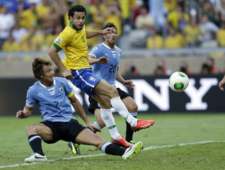 Brazil's Fred scores a goal between Uruguay's Diego Lugano and Alvaro Gonzalez during their Confederations Cup semi-final soccer match at the Estadio Mineirao in Belo Horizonte