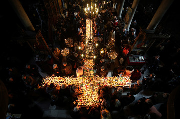 Worshippers gather around candles stuck to jars with honey in the church of the Presentation of the Blessed Virgin in Blagoevgrad