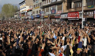 Kashmiri people raise their arms during funeral of Moulana Showkat Shah in Srinagar