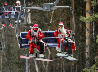 Snowboarders dressed as Ded Moroz, Russian equivalent of Santa Claus, ride a lift uphill during the Ded Moroz and Snegurochka Night to mark the upcoming New Year celebration in the suburbs of Krasnoyarsk