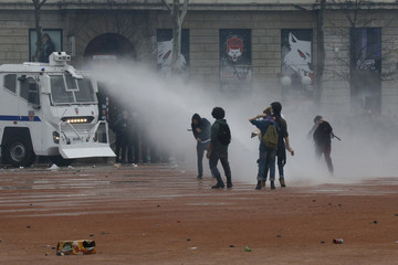 French police direct a water cannon towards youths during a demonstration by employees, high school and university students against the French labour law proposal in Lyon