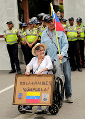 """An opposition supporter in a wheelchair carries a sign with a Venezuela's constitution glued to it and that reads """"Do not change it, obey it!"""" while rallying against President Nicolas Maduro in Caracas"""