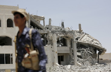 A Houthi militant walks at the yard of residence of the military commander of the Houthi militant group, Abdullah Yahya al Hakim, after it was hit by an airstrike, in Sanaa