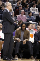 Raptors' Bosh watches from the bench behind Raptors' head coach Triano during their NBA basketball game against the Wizards in Toronto