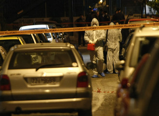 Police experts search for evidence at a street where a bomb exploded in Athens