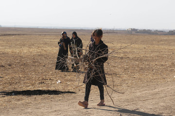 Displaced people from the outskirts of Mosul carry firewood in the town of Bashiqa, after it was recaptured from the Islamic State, east of Mosul