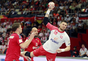 Grabarczyk of Poland attempts to score past Evdokimov and Igropulo of Russia during their preliminary round of the 24th men's handball World Championship in Doha