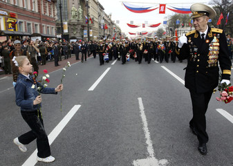 A girl presents a flower to a World War Two veteran during a march in the centre of St. Petersburg