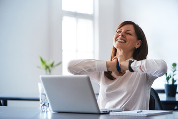 Excited woman working at desk in office. Using antistress ball.