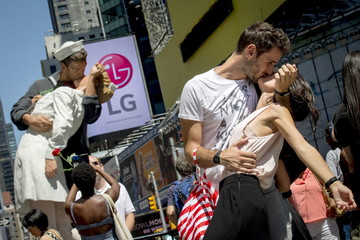Couple poses for friends to reenact the famous picture of a sailor kissing a nurse on the 70th anniversary of Victory over Japan Day near a replica sculpture in New York's Times Square