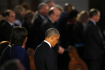 U.S. President Barack Obama and his wife Michelle bow their heads at an interfaith memorial service for the victims of the bombing at the Boston Marathon in Boston