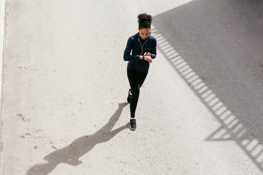 Young woman in sportswear walking on street and looking on her activity tracker