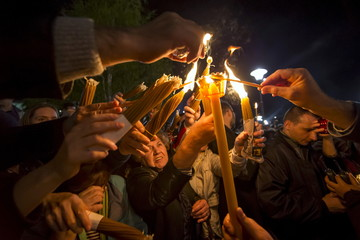 Worshippers light candles in front of St. Sava temple during an Orthodox Easter service in Belgrade