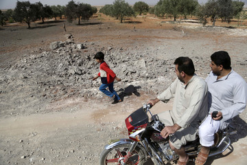 Men ride a motorbike as a boy runs at a site hit overnight by what activists said were airstrikes carried out by the Russian air force near a camp for displaced people on the outskirts of al-Ghadfa