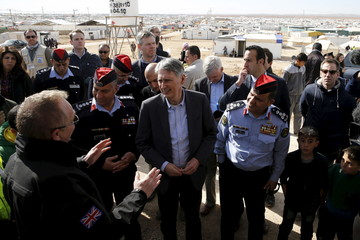 Britain's Foreign Secretary Philip Hammond speaks with former British police officers, who are working with Jordanian police officers to train and support the Community Police, during his visit to Al Zaatari refugee camp in Mafraq, jordan