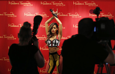 Media members photograph a wax figure of singer Rihanna as it is unveiled at New York City's Sacred Tattoo NYC shop