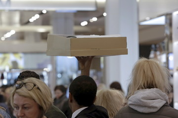 A staff member lifts a shoe box at Macy's Herald Square store during the early opening of the Black Friday sales in the Manhattan borough of New York