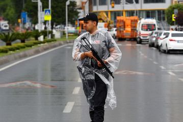 A police officer stands guard near the site where a Turkish police bus was targeted in a bomb attack in Istanbul