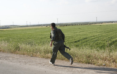 A Syrian soldier runs to secure a convoy of UN observers during their field visit to the northern province of Idlib