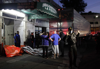 File photo of police officers standing next to a truck, containing 76 bodies found in mass graves in northern Mexico, parked outside the La Piedad embalming building in Mexico City